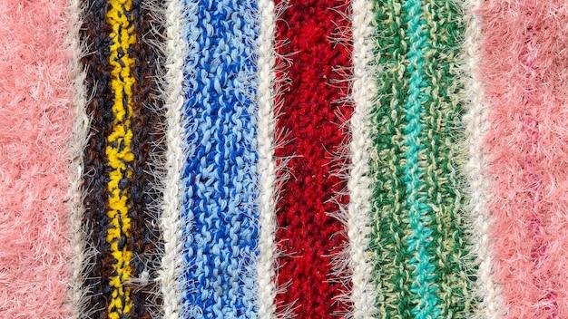 Различные цветные полоски на поверхности трикотажного полотна. фон крупным планом текстиля ретро ковры или коврики. текстура ткани сочетается с геометрией линий. изделие ручной работы