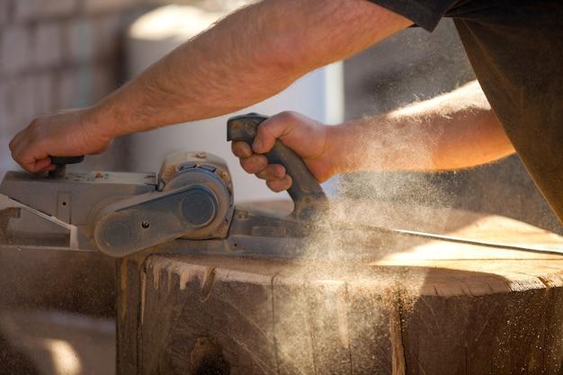 Плотник работает с электрическим рубанком на деревянном пне на открытом воздухе
