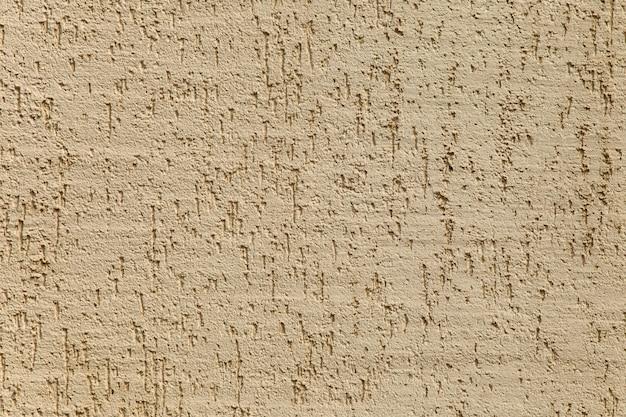 Текстурированная бетонная штукатурка бежевого цвета на стене. наружная отделка дома защита здания от агрессивной среды. безопасный зоологический чистый материал для фасадов