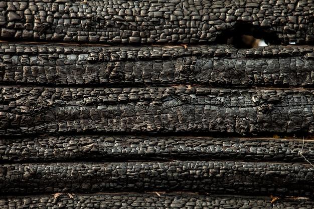 黒焦げの焦げた木製の壁。汚れた質感