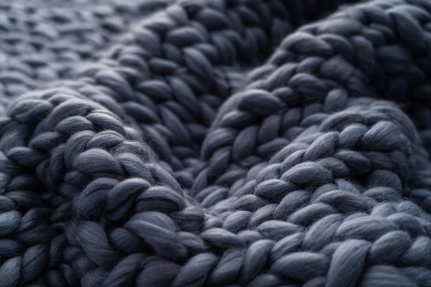メリノウールの手作りニットの大きな毛布、極太の糸、トレンディなコンセプト。ニット毛布、メリノウール背景のクローズアップ。ベージュのスモーキーウール製のデザイナーブランケット