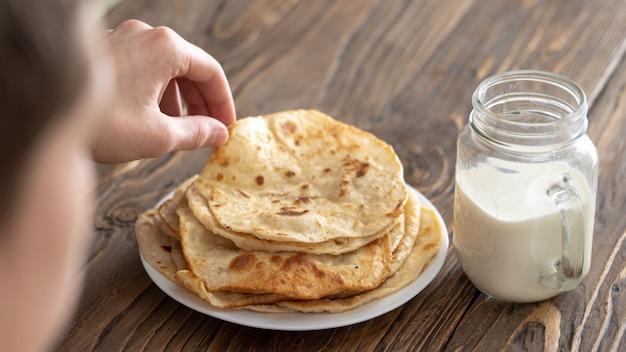 男は朝食、牛乳のマグカップ、揚げたトウモロコシのトルティーヤのプレートを彼の肩越しに見ている木製の質感のテーブルの上に持っています。フリーテキストコピースペース