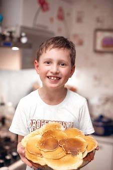子供はパンケーキのプレートを保持しています。