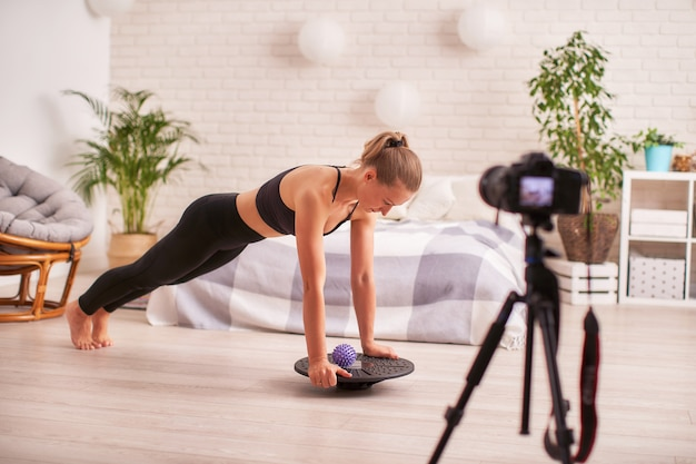 Женщина делает упражнения на специальном симуляторе балансировки.