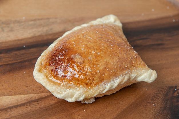 ペルーの伝統的なお菓子:「エンパナーダデカルネ」。甘い甘い。木製の背景。上面図。