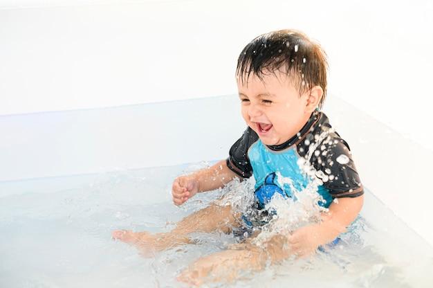 Ребенок улыбается и наслаждается водой в бассейне