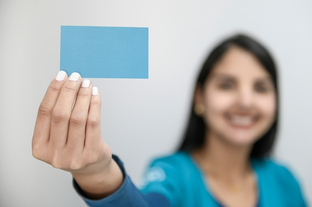 Красивая молодая женщина с большой улыбкой, отображение пустой визитной карточки