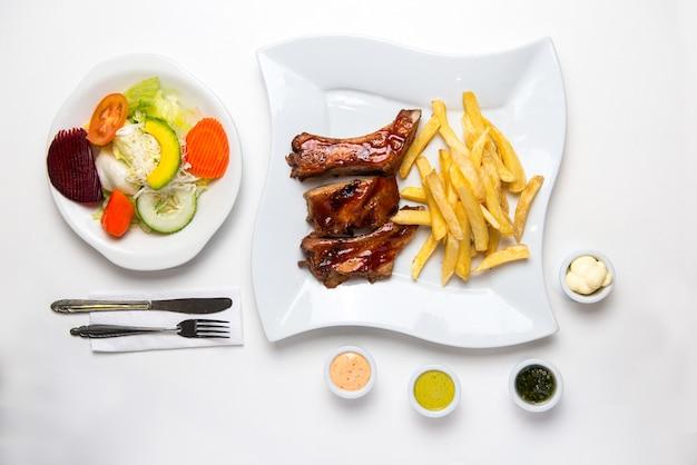 Барбекю ребрышки с картофелем фри, салатом и сливками. барбекю