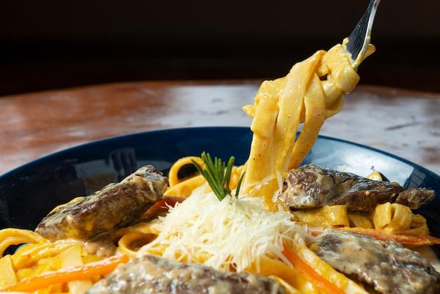 肉とチーズの麺を保持しているフォーク。