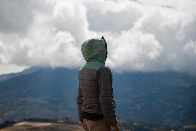 Человек с капюшоном созерцает горный пейзаж.