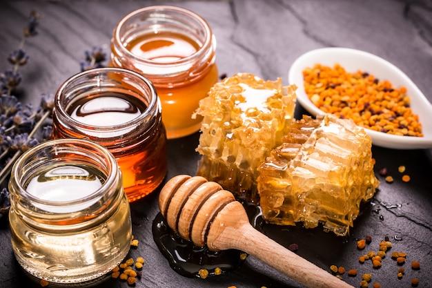黒い石の上に蜂蜜ディッパーと瓶の蜂蜜