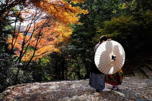 京都嵐山の公園で結婚式前の写真撮影のためにポーズをとって伝統的な着物の結婚式のカップル