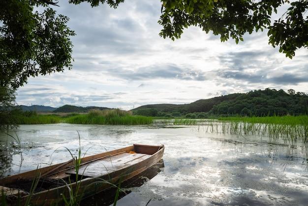 雲と空の反射でいっぱいの空に浮かぶボートのある湖
