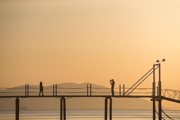 夕日の海に架かる橋で写真を撮る恋人たちのシルエット