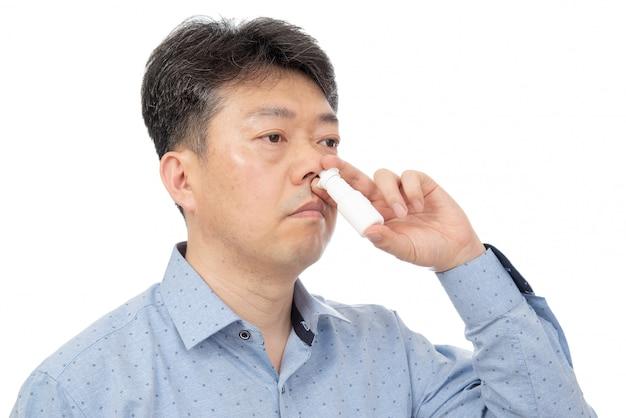 鼻スプレーを手に持った男