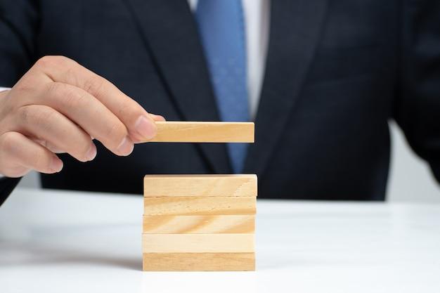 テーブルの上の木製のブロックをスタッキングの実業家の手。事業コンセプト。