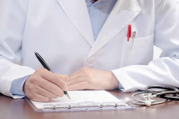 近くの聴診器で医療フォームに書いている男性医師。
