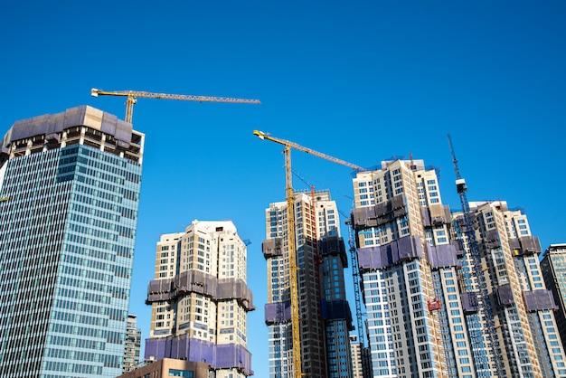 タワークレーンで建設中の近代的な高層ビル。産業コンセプト。