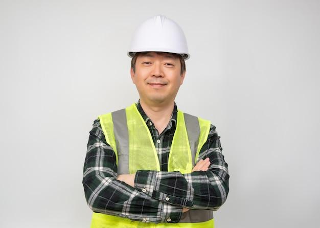 ライトグリーンの作業ベストと白い安全帽子のアジアの中年男。
