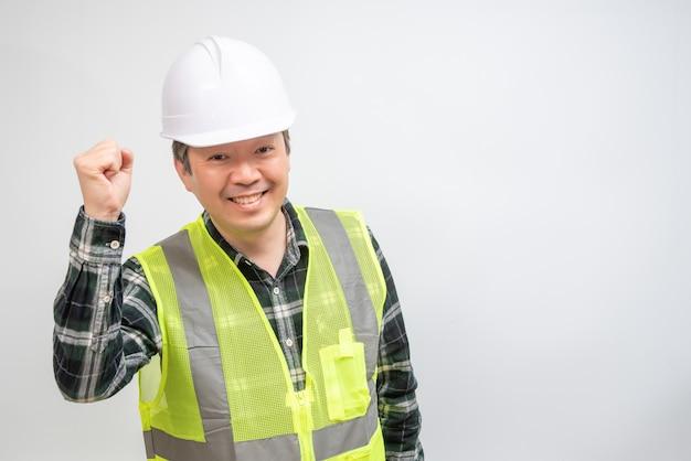 Азиатский мужчина средних лет в светло-зеленом рабочем жилете и белой шляпе безопасности.