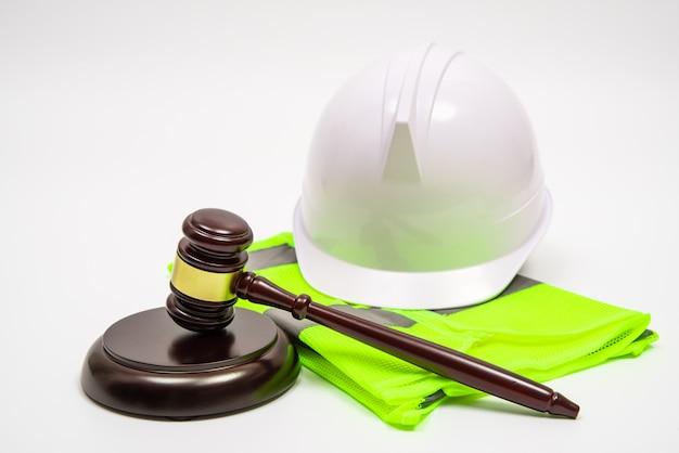 Трудовая правовая концепция с защитными шляпами, рабочей одеждой и молотком судьи на белом фоне.