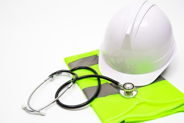 白い背景には、安全帽子、作業服、聴診器があります。コピースペース付き。