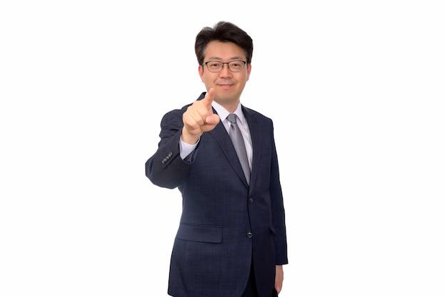 Азиатский средн-постаретый бизнесмен делая жесты рукой на белой предпосылке.