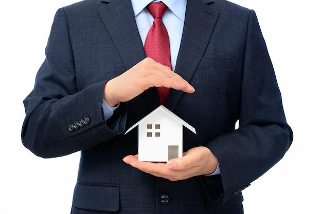 一方で家のモデルを持ったビジネスマン。不動産のコンセプト。