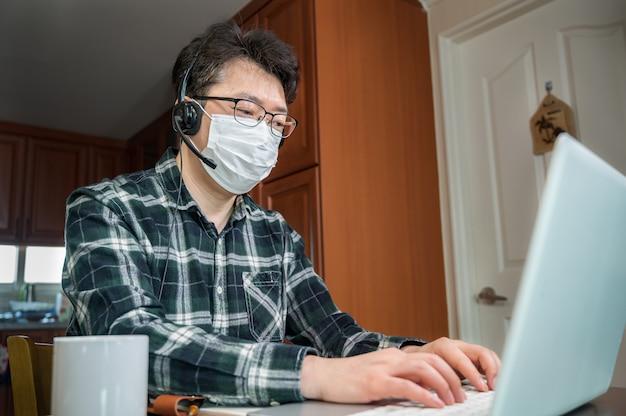 大規模なパンデミックのために自己隔離され、自宅で働いているアジア人男性。