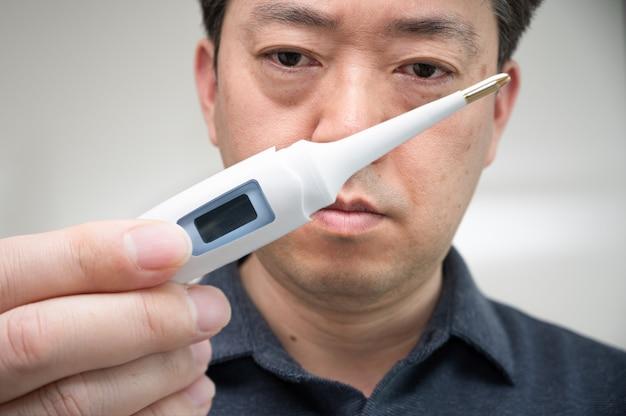 Азиатский мужчина средних лет, который с тревогой смотрит на градусник в руке
