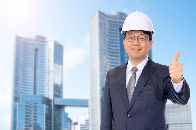 Азиатский бизнесмен средних лет улыбается в белой каске перед современным зданием.