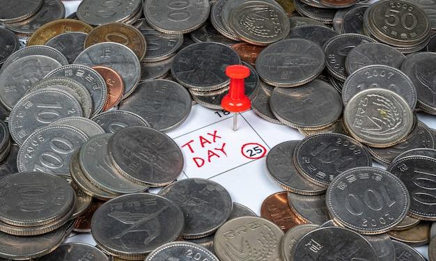 Налоговый день написан на календаре с красной канцелярской кнопкой.