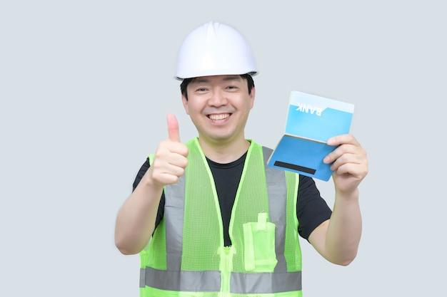 Азиатский инженер средних лет держит банковскую книжку