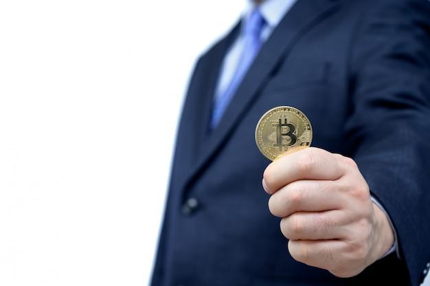 Золотой биткойн в мужской руке. блокчейн и новая виртуальная валюта.