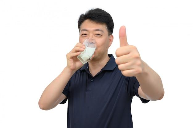 Азиатский мужчина средних лет пьет свежий стакан молока на белом
