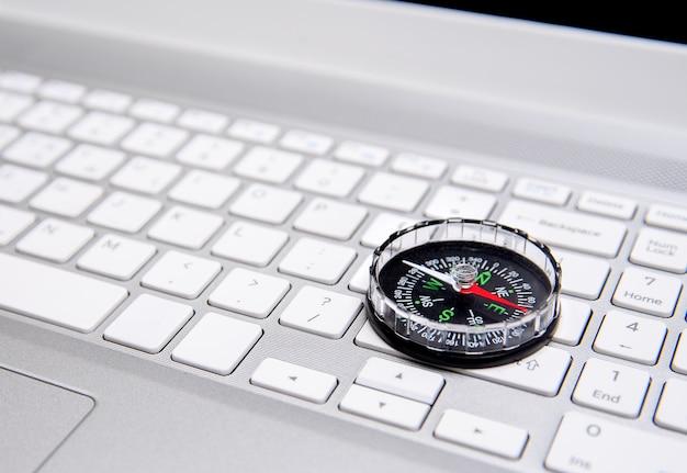 ノートパソコンのキーボードとコンパス、インターネットナビゲーションの概念。