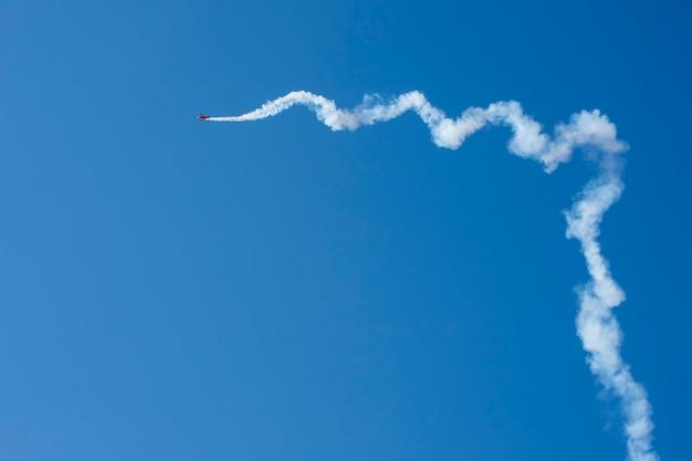 Самолет отстает на голубом небе с космосом экземпляра.