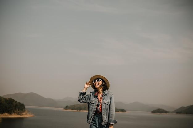湖でリラックスした若い女性。彼はサングラスと帽子をかぶっています。
