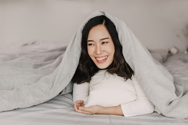朝のアジアの女性の正面図。彼女は新しい一日を始めるのに完全に満足して笑っている