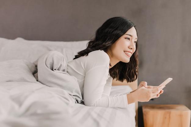 Проснувшись, азиатская женщина улыбается держит мобильный телефон на кровати. она смотрит за пределы своей комнаты.