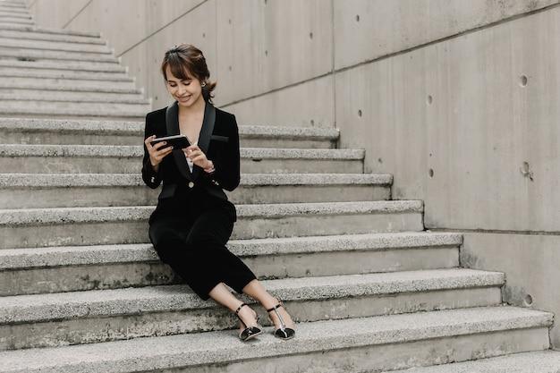 アジアビジネスの女性は笑みを浮かべて、階段に座っています。彼女は上司とチャットしています