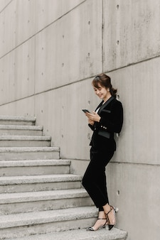 Азиатская бизнес-леди в чате и стоя на лестнице