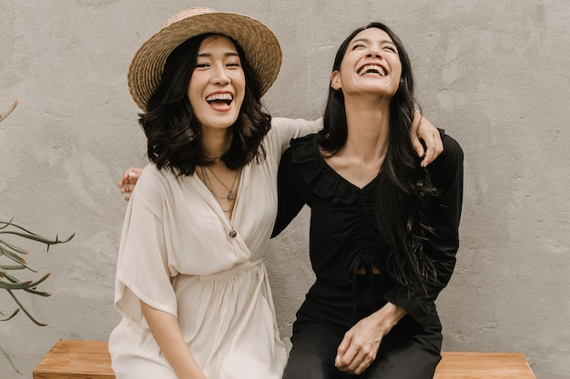Две азиатские женщины обнимаются вместе, пока они смеются и улыбаются