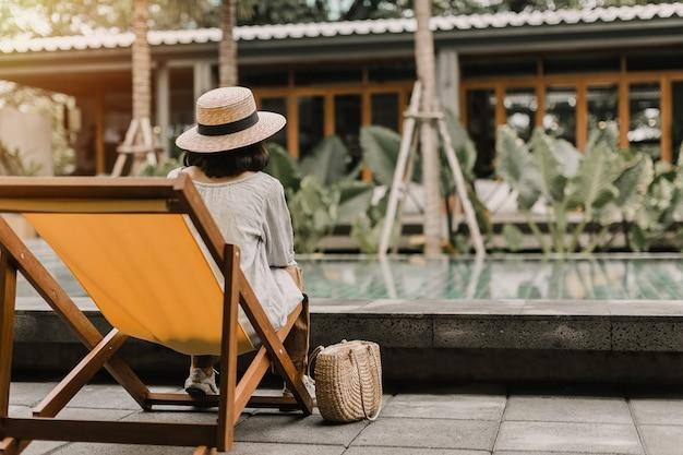 スイミングプールのそばの帽子リラクゼーションを着ている女性。彼女はオレンジ色のデッキチェアに座っています。