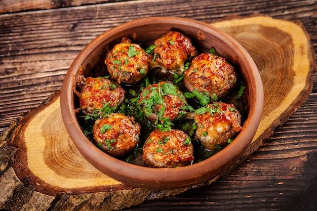 グルジア料理のコンセプト。焼きキノコのシャンピニオンと肉とコリアンダー。赤い粘土で作られたプレートのレストランで料理を提供します。木製の背景に。コピースペース