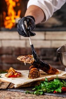 Шеф-повар готовит мясо люля кебаб в тесте на гриле.