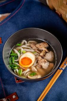 アジア料理のコンセプト。中華麺、卵、鶏肉、ねぎ入りの日本のラーメンスープ。ボウルのレストランで料理を提供します。背景画像。コピースペース
