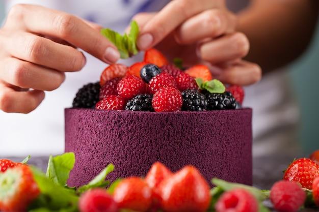 シェフがケーキの野生の果実を飾る