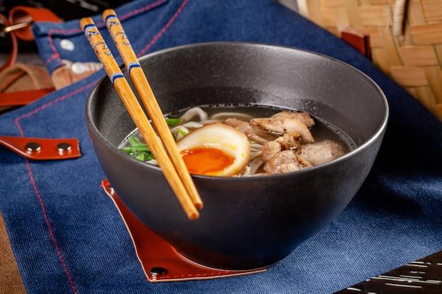 中華麺、卵、鶏肉、ねぎ入りの日本のラーメンスープ。
