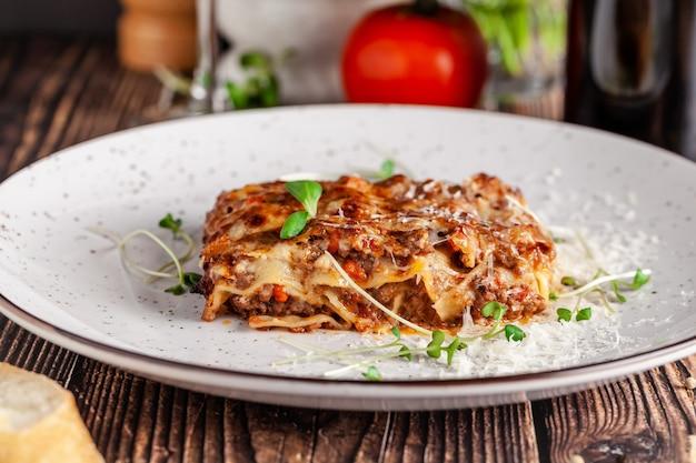 Концепция итальянской кухни. лазанья с мясным фаршем, соусом бешамель и сыром пармезан. закройте сервировка блюд в ресторане в белом блюде. копировать пространство